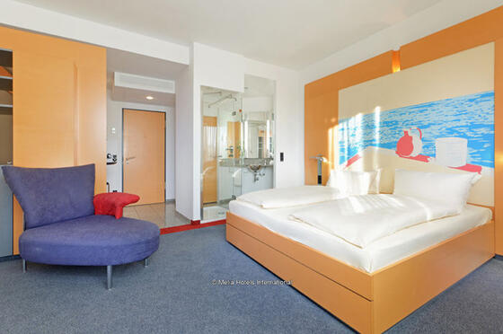 A spacious room with a large bed and room amenities at Precise H