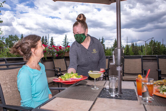 The waitress serves food for the woman at Sophie Station Suites