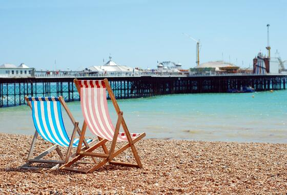 Two beach chairs at the coast of the beach facing the Brighton P