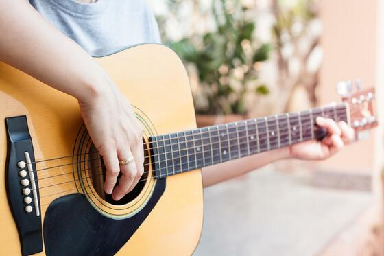 Close-up picture of a person playing the guitar