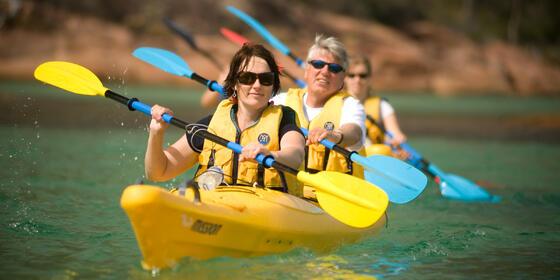 view of Ladies kayaking at the bay near Freycinet Lodge