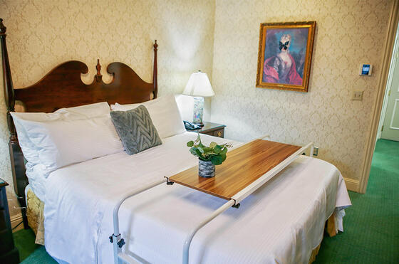 Large bed with rolling table over it and a small plant on top