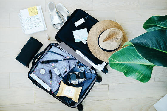 Open suit case with travel items for vacation