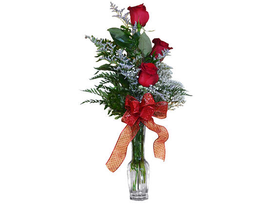 Three roses arranged in a vase with a red bow