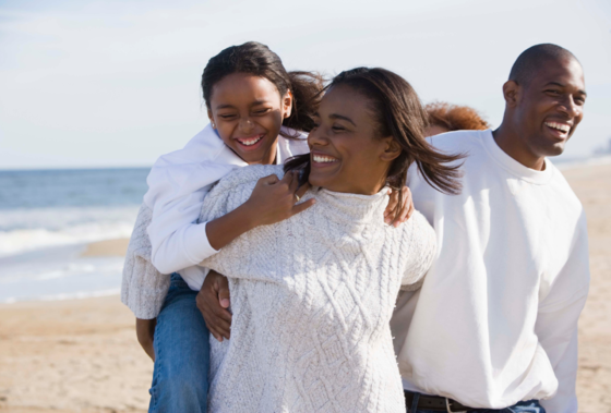 family laughing on beach