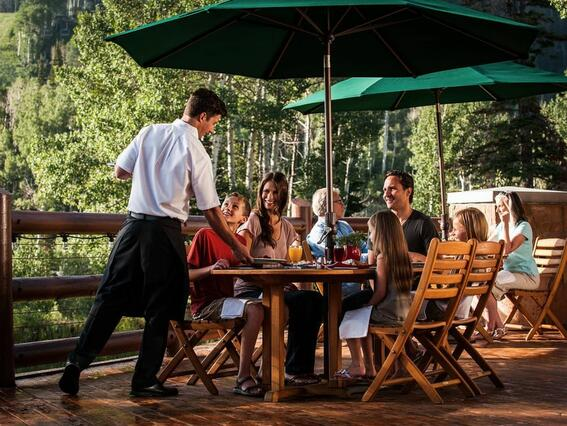 a waiter serving a family at an outside table