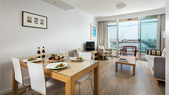 Dining area and living area in an apartment at Be Fremantle
