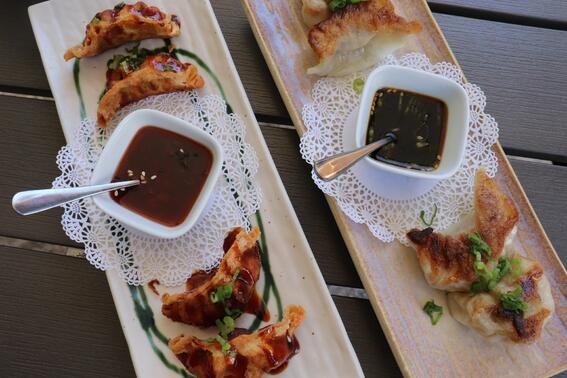 two plates of fried dumplings with dipping sauce