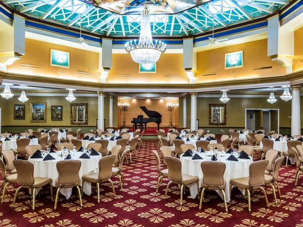 Ballroom with round conference tables and grand piano.