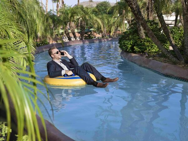 Business man in lazy river on cell phone
