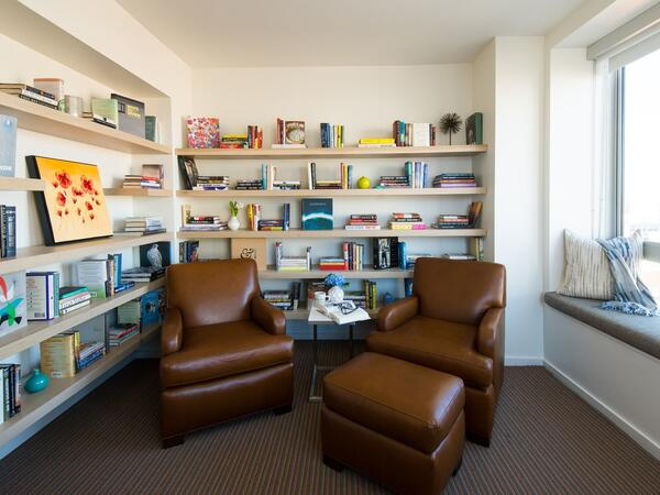 Leather chairs in den with wall book shelves