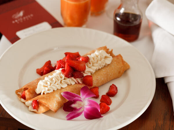 Rolled crepes topped with whipped cream and strawberries