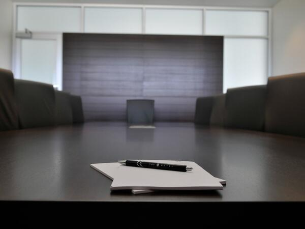 Pen and paper on large boardroom table