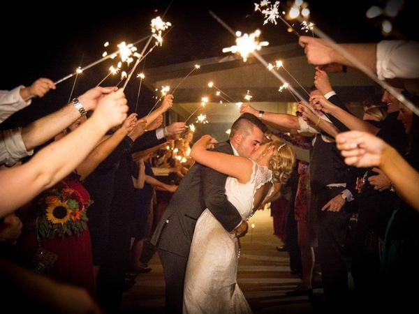 Newlyweds under sparklers.