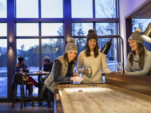 Friends playing on a shuffleboard table.