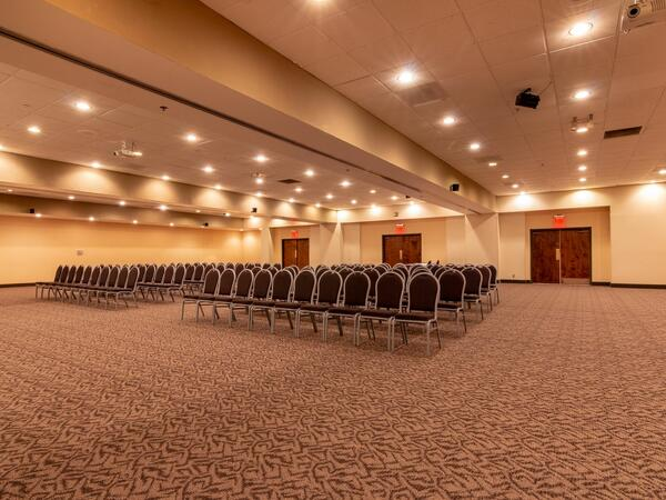 Large ballroom with seating, podium and projection screen.