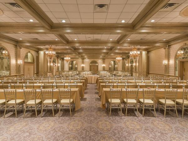 Decadent ballroom lined with chairs and tables