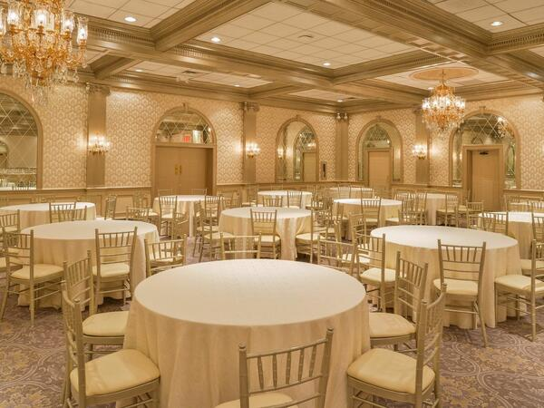 Decadent ballroom lined with round tables