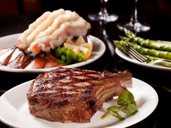 Several dishes including a ribeye steak.