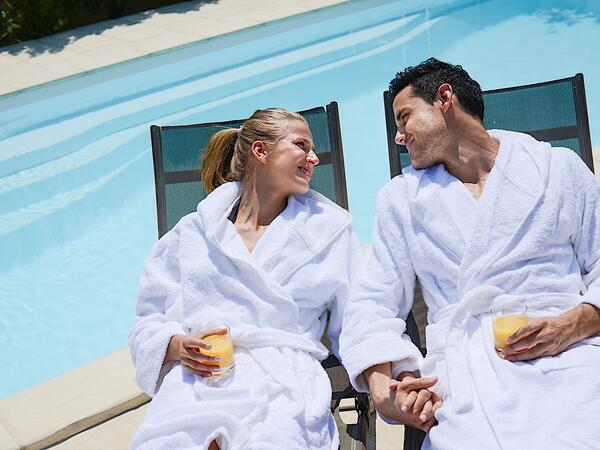 Couple in spa robes sipping cocktails.