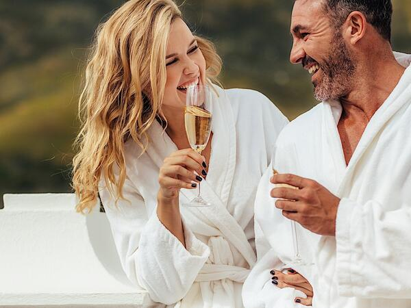 Couple in spa robes drinking champagne.