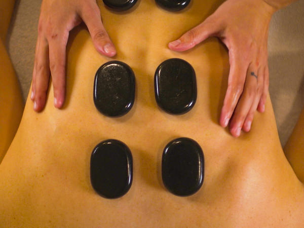woman getting a massage with black stones on her back