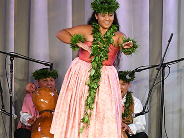 woman wearing leis performing on state