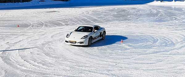 Un voiture de course blanche faisant un dérapage sur la glace