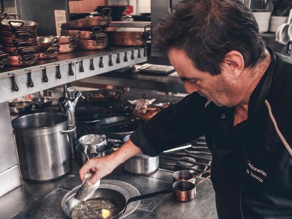 Le chef Claude TRINCAZ préparant la cuisson d'un poisson