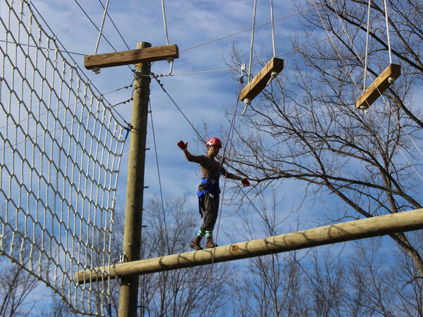 Person walking on log in the air at a ropes course