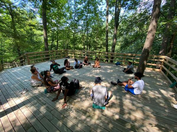 People sitting in circle on outside wooden deck