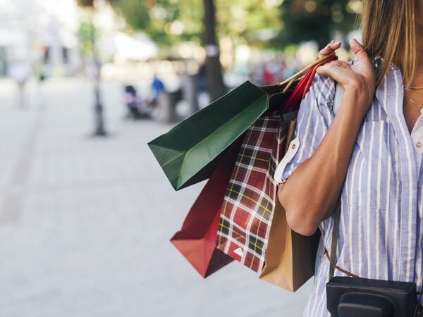 A lady carring shopping bags in different colors