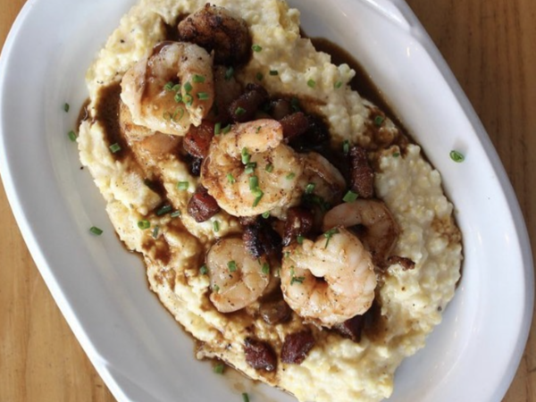An blue collar restaurant grits and prawns  dish with gravy