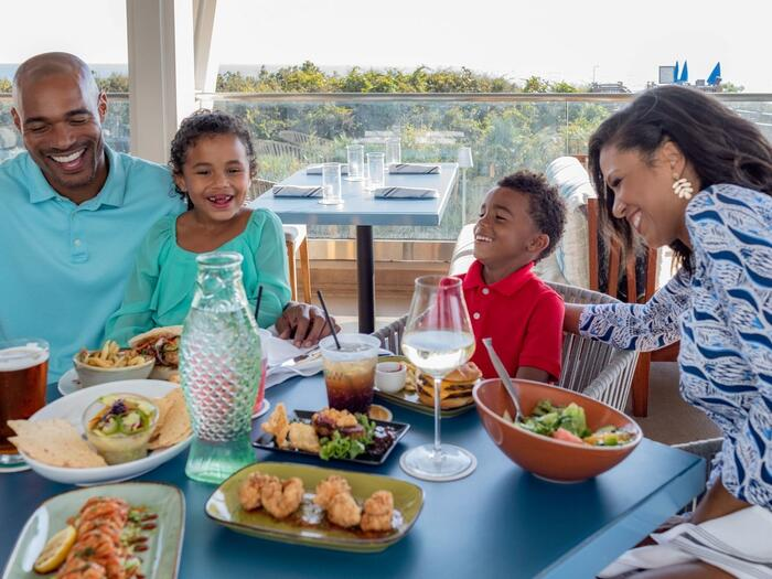 Family at a patio table with a full serving of food