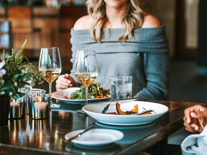 Couple at a classy restaurant table with food and wine.