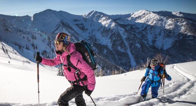 Deux femmes qui monte en ski de randonnée sous le soleil