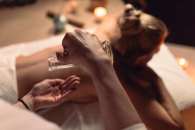 La masseuse verse de l'huile dans ces mains avant un massage