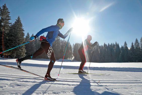 Deux personnes faisant de la course en ski de fond au soleil
