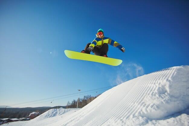 Personne en snowboard sautant une bosse
