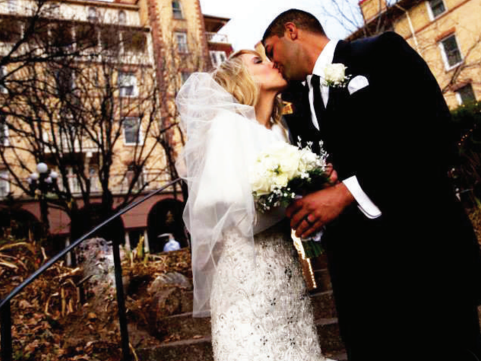 Bride and groom kissing outside of hotel