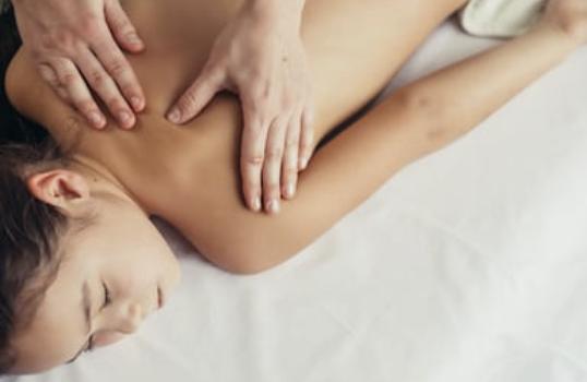 Un enfant reçoit un massage du dos