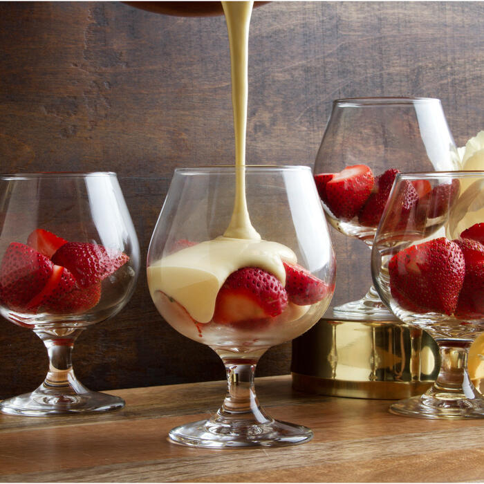 Cream being poured over strawberries in multiple brandy glasses