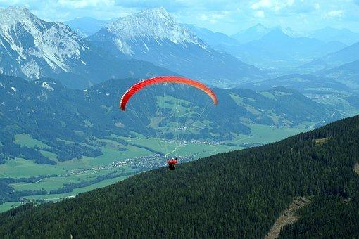 Une personne avec un parapente rouge dans les aires
