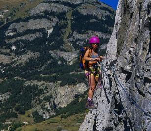 Une femme avec un bordier traversant le flan d'un montagne