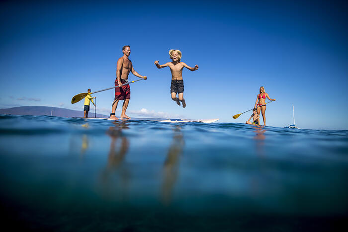 boy jumping off paddleboard into ocean