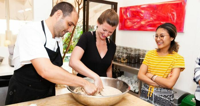 chef teaching students to cook in kitchen