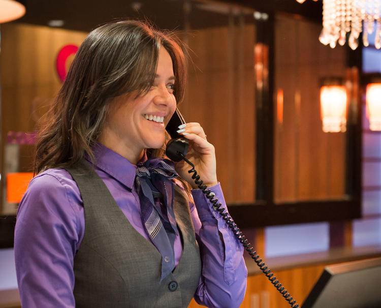 Hotel concierge smiling and speaking on phone