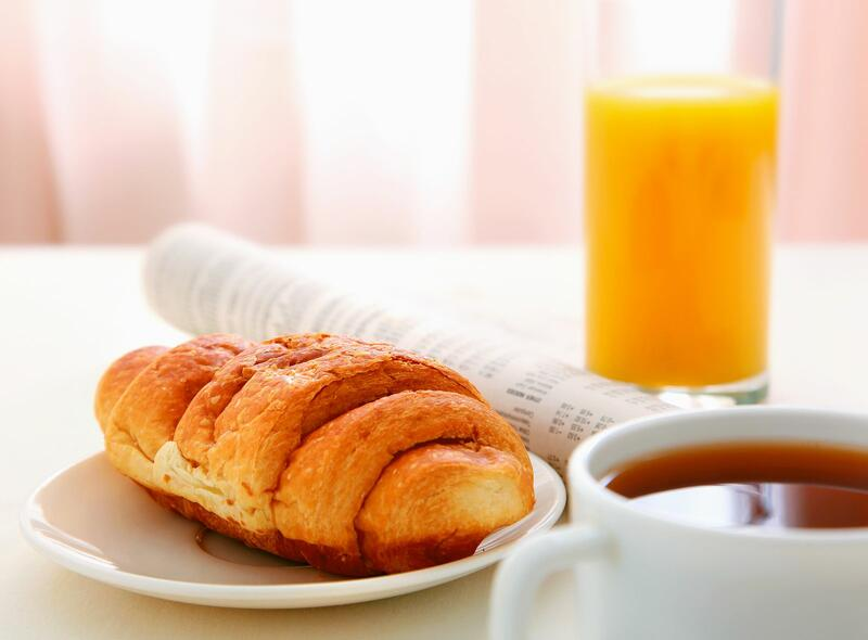 Photo of a croissant, orange juice, and coffee