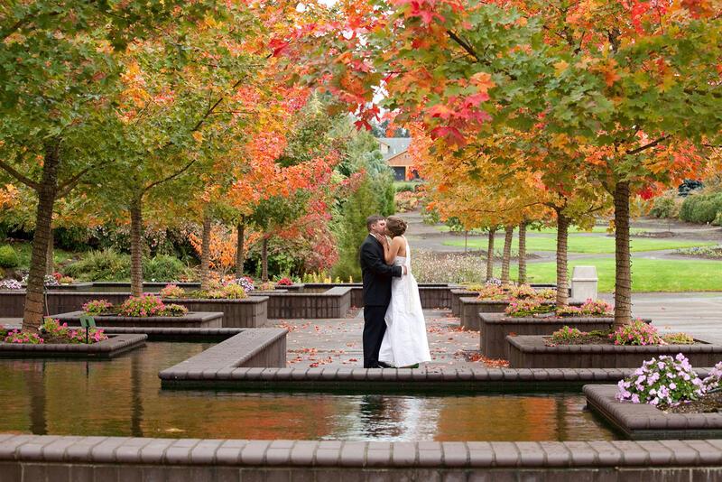 Groom kisses bride under trees