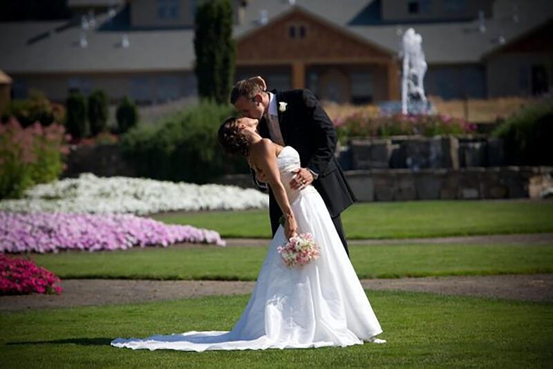 Groom kisses bride in front of garden